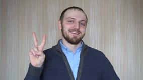 Portret młody brodaty mężczyzna gestykuluje zwycięstwo znaka, indoors zbiory wideo