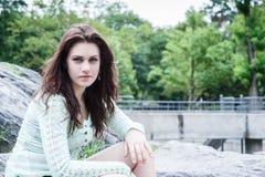 Portret młody brunetki obsiadanie na bouders Zdjęcia Royalty Free