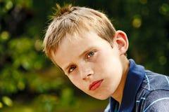 Portret młody chłopiec obsiadanie w ogródzie Zdjęcia Stock