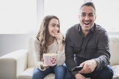 Portret młody człowiek ogląda TV córka i podczas gdy jedzący popkorn na kanapie obrazy stock