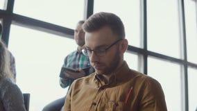 Portret młody człowiek siedzi przy loft biurem przy biznesowym konwersatorium Samiec z grupą ludzi słucha mówcy, robi notatkom zdjęcie wideo