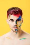 Portret młody człowiek z barwioną twarzy farbą na żółtym tle Fachowa Makeup moda Fantazi sztuki makeup Zdjęcie Stock