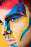 Portret młody człowiek z barwioną twarzy farbą na żółtym tle Fachowa Makeup moda Fantazi sztuki makeup Zdjęcie Royalty Free