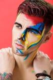 Portret młody człowiek z barwioną twarzy farbą na czerwonym tle Fachowa Makeup moda Fantazi sztuki makeup Zdjęcia Royalty Free