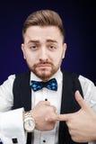 Portret młody człowiek z brodą pokazuje zegarek na ciemnym backgro fotografia royalty free