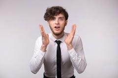 Portret młody człowiek z szokującym emocjonalnym ręka gestem nad światłem i wyrazem twarzy - szary tło obraz stock