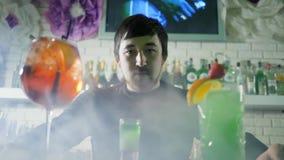 Portret młody facet przy kontuarem z barwionym alkoholu napojem z owoc na tle prętowy wnętrze w mgle zdjęcie wideo
