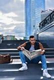 Portret młody facet w skórzanej kurtki czytelniczej gazecie w cit fotografia royalty free
