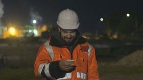 Portret młody i szczęśliwy pracownik budowlany w hełmie przy nocą używać telefon zbiory wideo