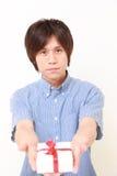 Portret młody Japoński mężczyzna oferuje prezent zdjęcia stock