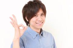 Portret młody Japoński mężczyzna pokazuje perfect znaka fotografia stock