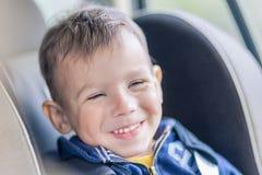 Portret Młody Kaukaski szczęśliwy Little Boy obsiadanie na samochód Sa Obrazy Royalty Free