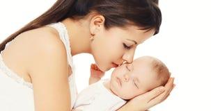 Portret młody kochający macierzysty całowanie jej dziecko na bielu zdjęcia stock