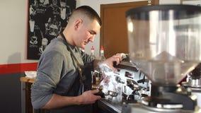 Portret młody męski barista pracuje z fachową kawową maszyną zbiory
