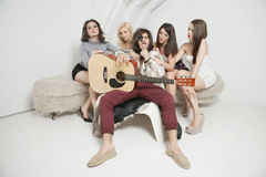 Portret młody męski gitarzysty obsiadanie wśród młodych żeńskich przyjaciół Obrazy Royalty Free