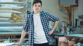 Portret młody męski pracownik, pozycja i patrzeć kamerę w warsztacie poważnie, Obraz Royalty Free