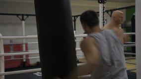 Portret młody męski pugilist który haczy czarną uderza pięścią torbę w bokserskim gym zbiory