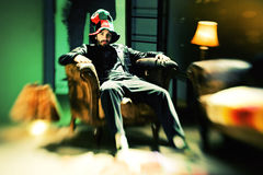 Portret młody modny mężczyzna obsiadanie w krześle jest ubranym ostrego kapelusz Zdjęcia Royalty Free