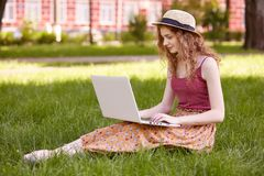 Portret młody nastolatka obsiadanie na zielonej trawie w parku z przenośnym komputerem na nogach, wydatki letni dzień plenerowy,  obraz royalty free