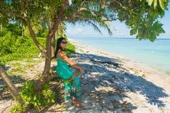 Portret młody piękny azjatykci dziewczyny obsiadanie w cieniu pod drzewem na tropikalnej plaży patrzeje stronę Zdjęcia Stock
