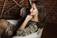 Portret młody piękny brunetki kobiety obsiadanie w krześle jako a Fotografia Stock