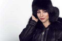Portret młody piękny uśmiechnięty model jest ubranym modną czarną skórę zapinał kurtkę i sobolowego futerkowego kapelusz fotografia stock