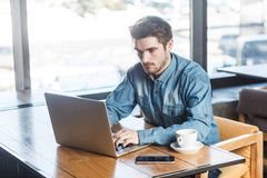 Portret młody pomyślny poważny brodaty biznesmen pracuje na komputerowym obsiadaniu w biurze zdjęcie stock