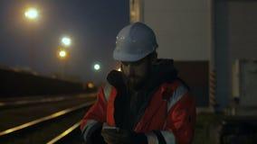Portret młody pracownik budowlany w hełmie używać telefon przy nocą 4K zbiory wideo