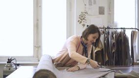 Portret młody projektant mody który pracuje w jej studiu z dużymi okno, zbiory