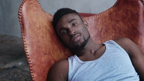 Portret młody przystojny afrykański mężczyzna obsiadanie na rzemiennym krześle i patrzeć kamerę Poważna wzorcowa samiec Zdjęcia Stock