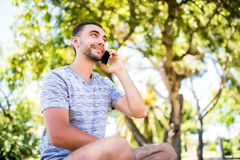 Portret młody przystojny młody człowiek opowiada na telefonie komórkowym fotografia stock