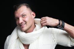 Portret młody przystojny mężczyzna, będący ubranym białego pulower i szalika odizolowywających na ciemnym pracownianym tle, zdjęcia royalty free