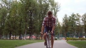 Portret młody przystojny mężczyzna jedzie rocznika bicykl przy parkową drogą Sporty faceta jeździć na rowerze plenerowy Zdrowy ak zdjęcie wideo