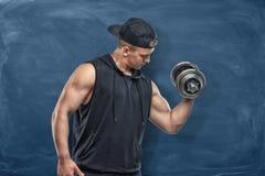 Portret młody przystojny mężczyzna stoi jego umięśnionych bicepsy i pokazuje podczas szkolenia w czarnym stroju Obraz Royalty Free