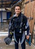 Portret młody przystojny mężczyzny nurek gotowy iść akwalungu pikowanie z zimna woda mokrym kostiumem, żebra, buoyancy kompensato obrazy stock