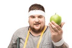 Portret młody pyzaty mężczyzna z pomiarowym taśmy mienia jabłkiem zdjęcia stock