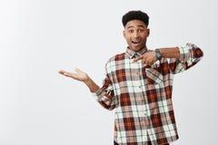 Portret młody rozochocony skinned śmieszny facet z afro fryzurą w w kratkę przypadkowym koszulowym udaje mieniu Zdjęcia Stock