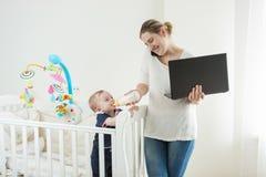 Portret młody ruchliwie bizneswoman pracuje na komputerze, opowiadający telefonem i karmieniem jej dziecko syn Zdjęcie Royalty Free