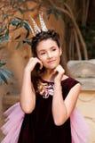 Portret młody słodki princess w koronie który zaaferowany nastroszony ona jej ręki twarz w nieśmiałym uśmiechu zdjęcia stock