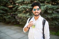 Portret młody studencki Indiański mężczyzna w okulary przeciwsłoneczni napoju lata napoju mojito w ulicach outdoors zdjęcia royalty free
