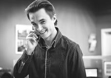 Portret młody uśmiechnięty facet opowiada na telefonie komórkowym w koszula w biurowym środowisku, czarny i biały wizerunek zdjęcia royalty free