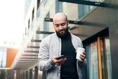 Portret młody uśmiechnięty mężczyzna używa smartphone na miasto ulicie Mężczyzna wysyła wiadomość tekstową lifestyle Og?lnospo?ec zdjęcia stock