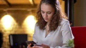 Portret młody z włosami bizneswoman attentively wykonuje transakcje używać kartę kredytową i smartphone zbiory