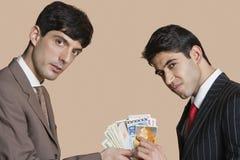 Portret młodzi biznesmeni pokazuje euro nad barwionym tłem Zdjęcie Royalty Free