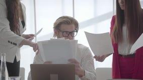 Portret m?cz?cy m??czyzny obsiadanie w wygodnym biurze z netbook przy sto?em egzamininuje dokumenty kt?re ?e?scy koledzy zbiory wideo
