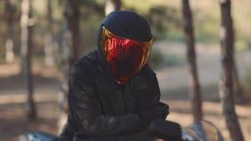 Portret m??czyzny motocyklista w czarnym he?mie przy zmierzchem Rowerzysta w lesie, koloru naliczek zbiory wideo
