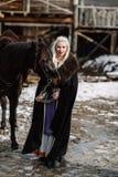 Portret młoda blond kobieta w czarnej pelerynie z koniem Zdjęcia Stock
