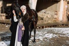 Portret młoda blond kobieta w czarnej pelerynie z koniem Obrazy Royalty Free