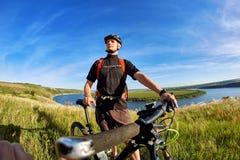 Portret młoda cyklista pozycja na wzgórzu nad rzeka przeciw niebieskiemu niebu z chmurami Zdjęcie Royalty Free