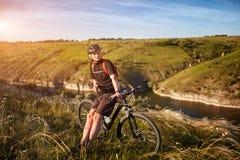 Portret młoda cyklista pozycja na wzgórzu nad rzeka przeciw niebieskiemu niebu z chmurami Fotografia Royalty Free